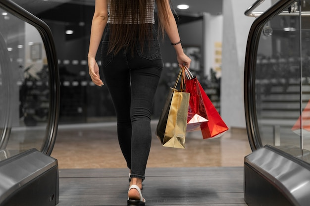 A woman with paper bags in her hands leaves the escalator. shopping mall concept. black friday