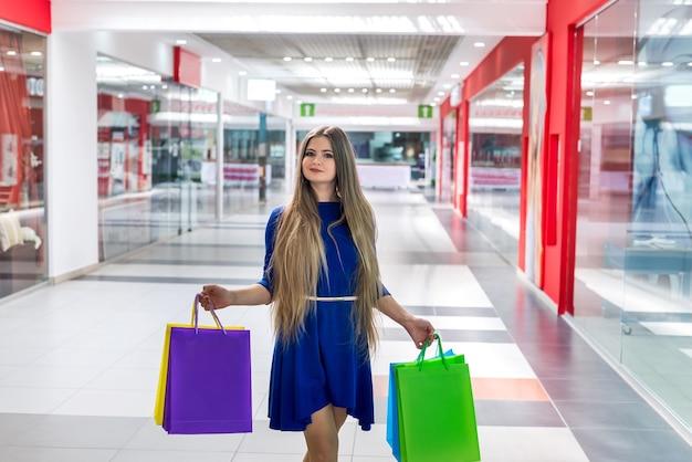 Женщина с бумажными пакетами позирует в большом торговом центре
