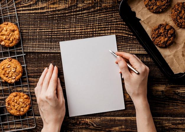 Женщина с бумажным листом и вкусным печеньем на столе