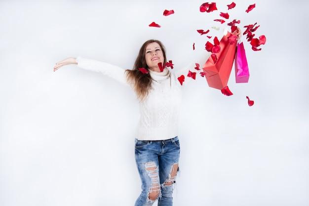 손에 종이 쇼핑백을 가진 여자, 즐겁게 떨어지는 장미 꽃잎을보고