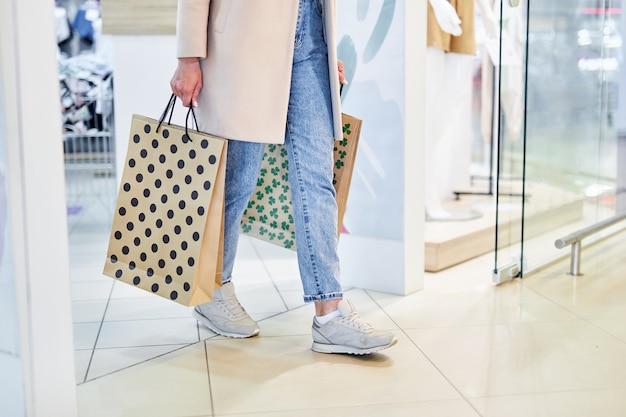 현대 쇼핑몰에서 걷는 종이 쇼핑백을 가진 여자. 가게에서 걷는 동안 쇼핑 가방을 들고 소녀입니다.