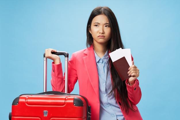 パスポートと飛行機のチケットの荷物の乗客の旅行を持つ女性