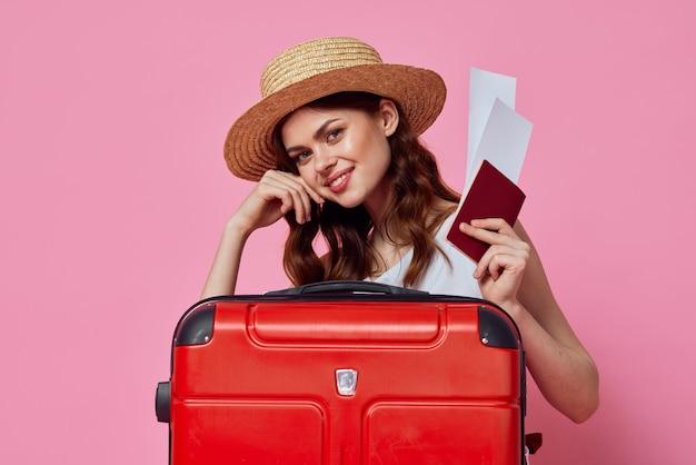 Женщина с паспортом и билетом на самолет красный чемодан отпуск пассажира крупным планом