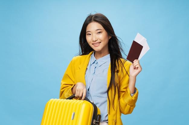 パスポートとチケットを持つ女性黄色のスーツケースジャケット青いシャツメイクモデル