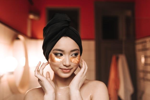 Donna con toppe sotto gli occhi e asciugamano sulla testa in posa contro il muro del bagno