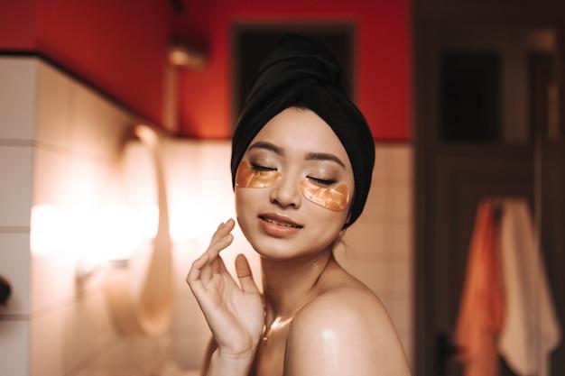 눈 밑에 패치가있는 여성은 몸과 피부에 대한 치료를 즐깁니다.