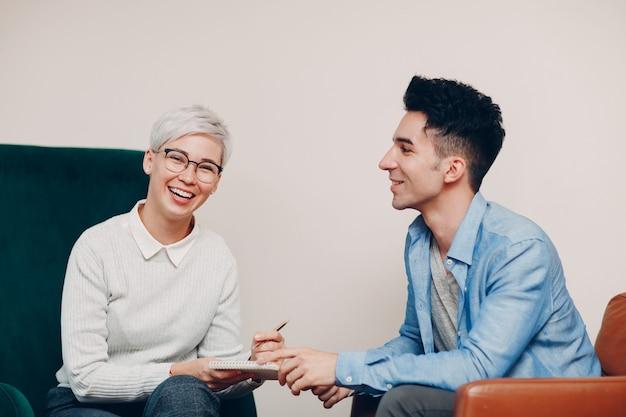 펜과 노트북을 손에 든 여자와 함께 의자에 앉아 웃는 남자. 저널리즘, 인터뷰 및 hr 고용 모집 설문 조사 계약 개념.