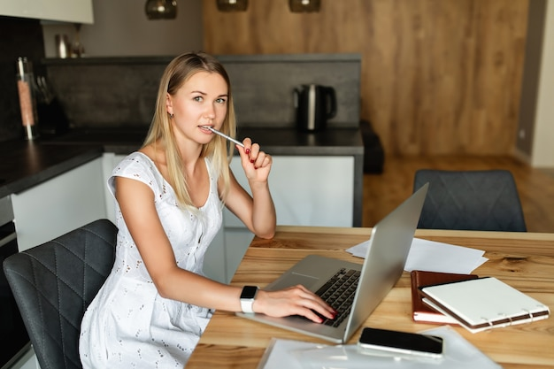 Woman with pen in mouth working on laptop computer at home office