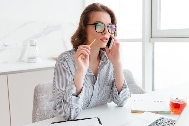 鉛筆を押しながら白い部屋の職場に座ってスマートフォンで話している物思いに沈んだ表情を持つ女性