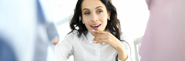 Женщина с задумчивым взглядом выбирает одежду на вешалке
