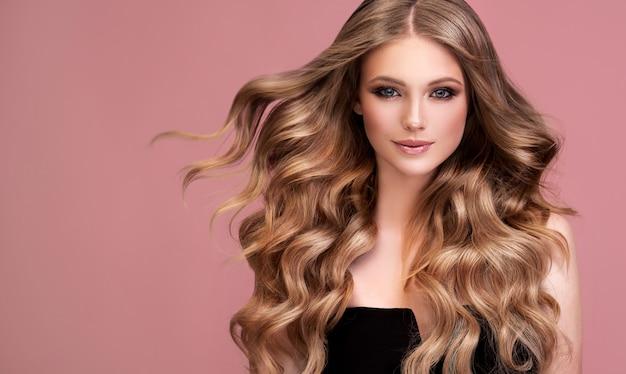 長くて青々とした深いブロンドの髪の完璧な密なカールを持つ女性フライングヘア理髪アートメイク