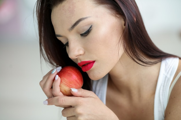 完璧な顔の皮膚とメイクアップのクローズアップ、リンゴを食べる女性