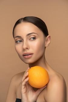Женщина с идеальной кожей лица, причесанными волосами, держит апельсин