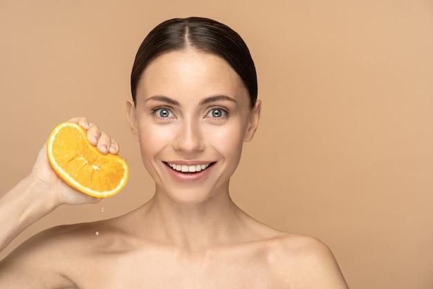 Женщина с идеальной кожей лица, причесанными волосами, выдавливающими апельсин. улыбающаяся женщина с естественным макияжем и цитрусовыми