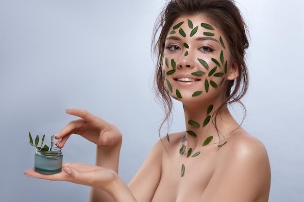 그녀의 얼굴에 녹색 잎을 가지고 크림을 들고 완벽한 피부를 가진 여자