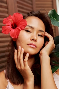Woman with perfect skin  and hibiscus flower in hairs posing over wood wall and tropical plants.