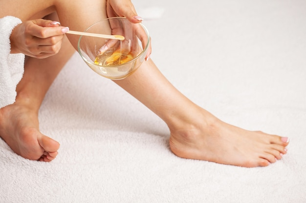 彼女の足に完璧な肌を持つ女性は、脱毛にワックスを適用しました