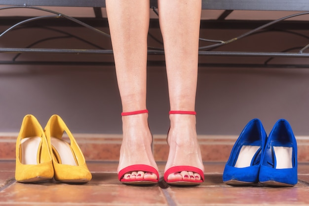 Woman with perfect slim legs, trying on different high heel shoes. shopping concept.