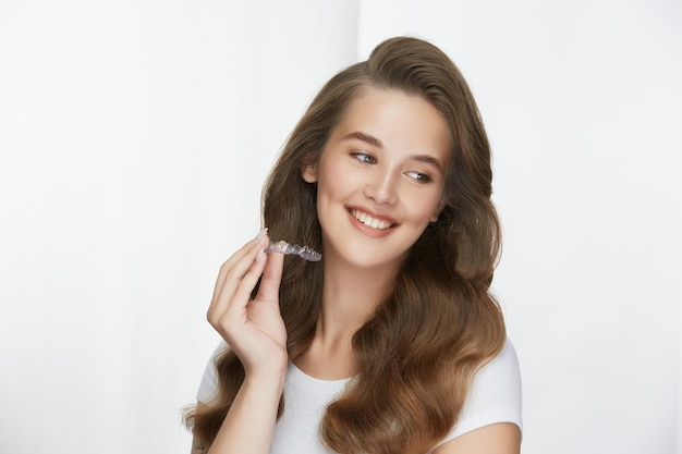 Woman with perfect white smile holding tooth cap and looking to side Premium Photo