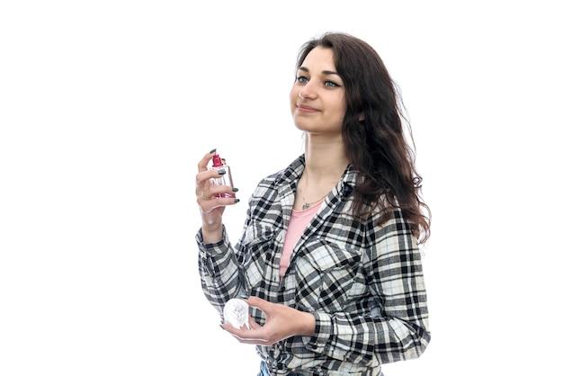 白で隔離の香水瓶を持つ女性