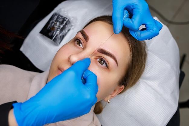 Женщина с татуировкой перманентного макияжа на бровях. косметолог крупным планом делает набросок бровей. профессиональный макияж и косметический уход за кожей.