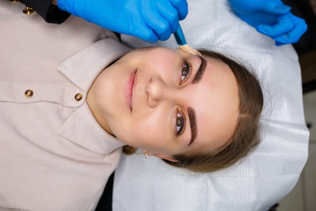 彼女の眉毛にアートメイクの入れ墨を持つ女性。クローズアップの美容師は、メイクアップに基礎を適用させます。プロのメイクアップと化粧品のスキンケア。