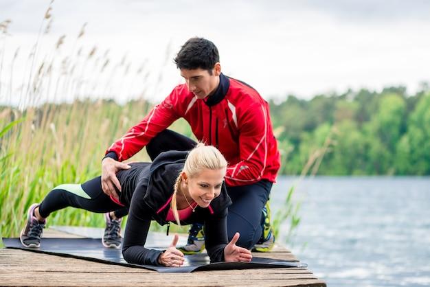 Женщина с личным тренером делает фитнес-отжимание