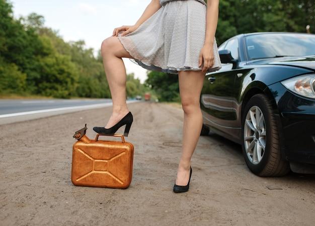 Женщина с канистрой бензина на дороге, поломка автомобиля, без газа. разбитый автомобиль или проблема с автомобилем, проблема с автомобилем на шоссе