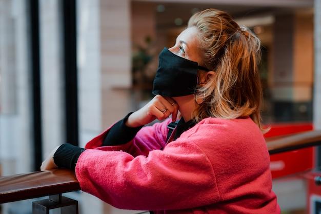 Женщина с телефоном ярко-розового пальто торгового центра с черной защитной маской на лице от зараженного вирусом воздуха.