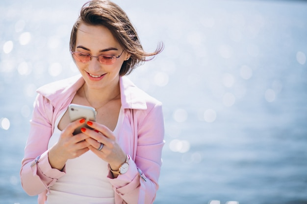 Woman with phone by ocean