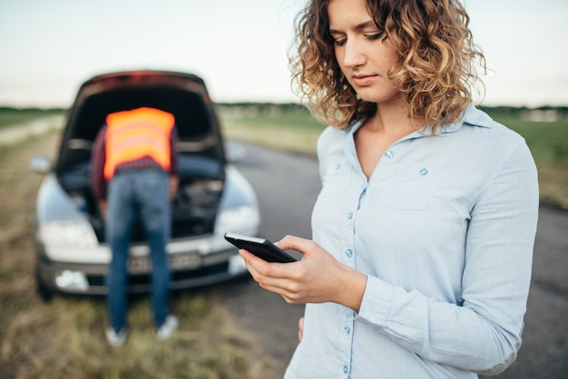 Woman with phone calls to emergency service, man tries to repair broken car.