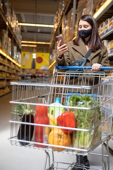 Woman with phone checking shopping list app in grocery store copy space