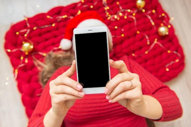 Woman with phone copyspase in hand santa hat lie on a soft merino wool blanket.