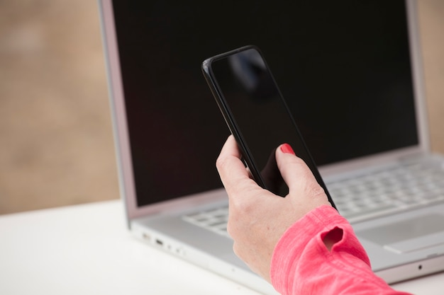 Женщина с телефоном в руке, рабочий стол на открытом воздухе с компьютером