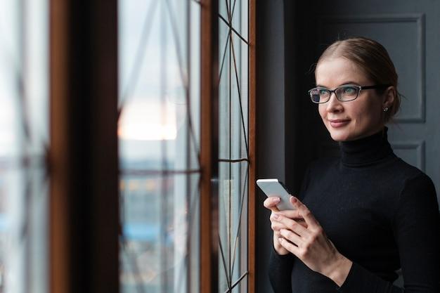 Donna con il telefono che osserva sulla finestra