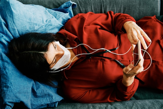 Woman with phone and mask on her couch during corona virus outbreak