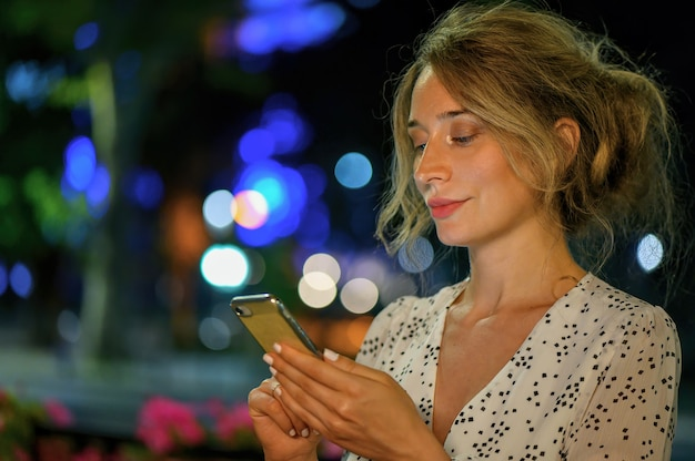 Woman with phone night portrait city lights bokeh.