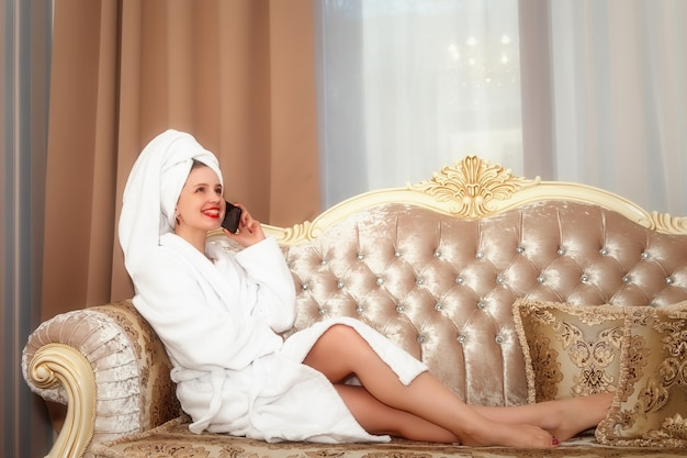 シャワーの後のホテルの部屋のソファーに電話を持つ女性