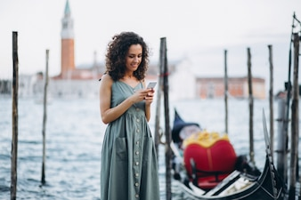 Woman with phone on vacation in Venice