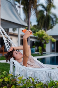 Donna con il telefono che riposa sdraiato sull'amaca con il telefono cellulare