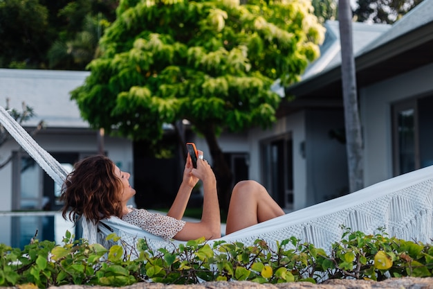 Woman with phone resting lying on hammock with mobile phone