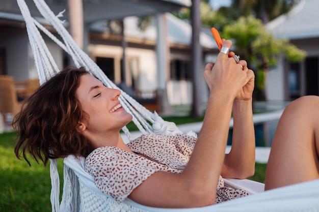 Женщина с телефоном, отдыхая, лежа на гамаке с мобильным телефоном