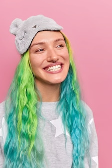 Woman with piercing in nose smiles broadly shows white teeth has good mood after healthy sleep dressed in nightwear isolated on pink