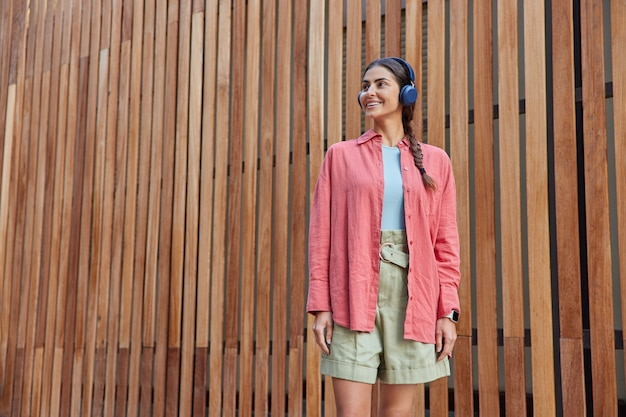 Woman with pigtail dressed in casual pink shirt and shorts listens music via wireless headphones smiles gently looks away stands on wooden hence enjoys favorite track from playlist