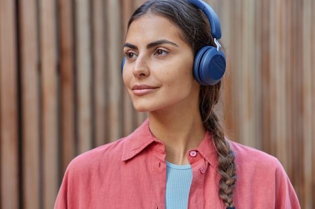 La donna con il codino ascolta la musica tramite le cuffie wireless gode di una playlist di musica preferita positiva focalizzata lontano vestita in camicia pone su sfocato