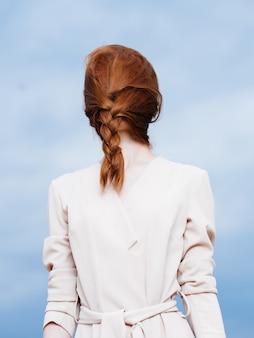 コート砂の自然の新鮮な空気で彼女の顔にピグテールを持つ女性