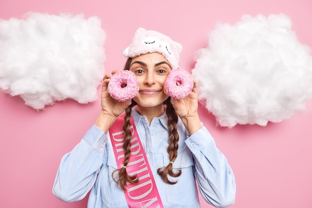 Woman with pigtails holds glazed doughnuts near face wants to eat bakery product wear sleepmask on forehead shirt and ribbon written word birthday poses around white clouds