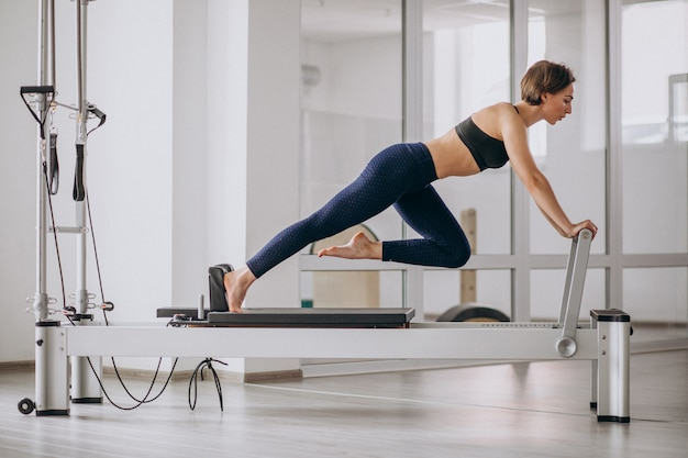 Woman with pilates trainer practising pilates