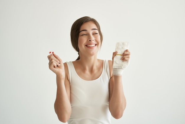 Женщина с таблетками в руках в белой футболке травмировала руку медицины здоровья