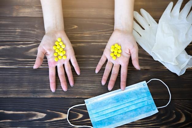 Женщина с таблетками в руках. медицинская маска и резиновые перчатки на фоне. вирусная болезнь. опасность пандемии коронавируса. грипп и простуда зимой.
